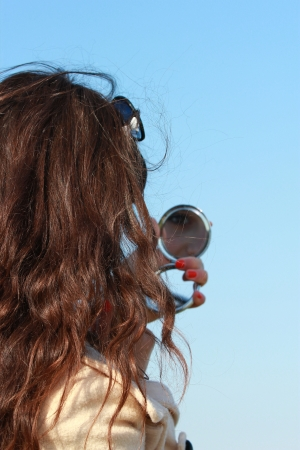 A young girl looks at herself in a small mirror photo