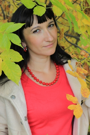 Portrait of a beautiful woman among the autumn leaves