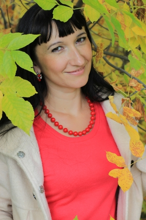 Portrait of a young woman among the autumn leaves Stock Photo