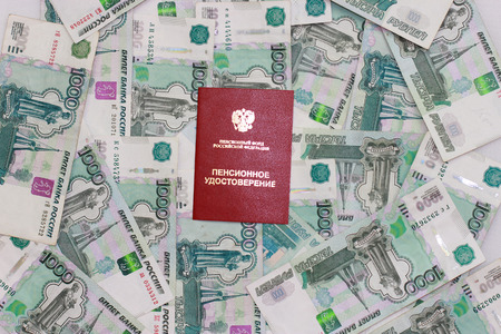 Pension certificate on the background of Russian bills