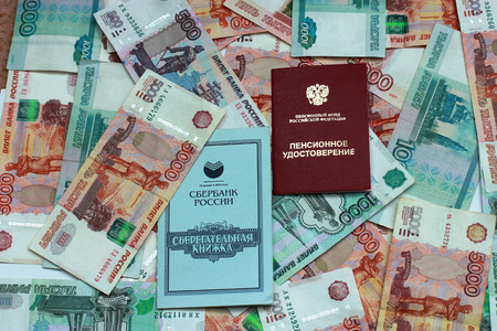 Pension certificate, savings book on the background of the Russian money