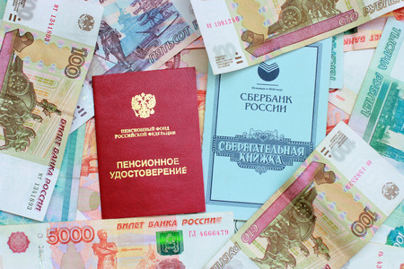 Pension card and savings book on the background of the Russian money
