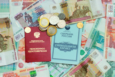 Pension card and savings book on the background of Russian money