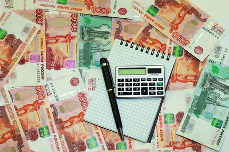 Pen, notepad and calculator lying on a background of Russian money