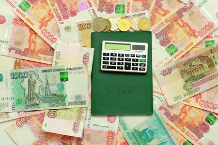 Calculator and employment history on the background of the Russian money Stock Photo