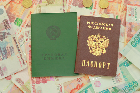 Work-book and a Russian passport lie on Russian money close up