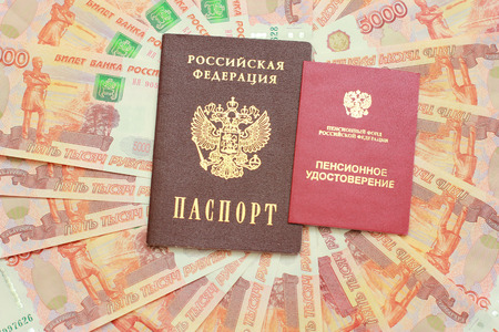 Passport and a pension certificate on the background of five thousandth money