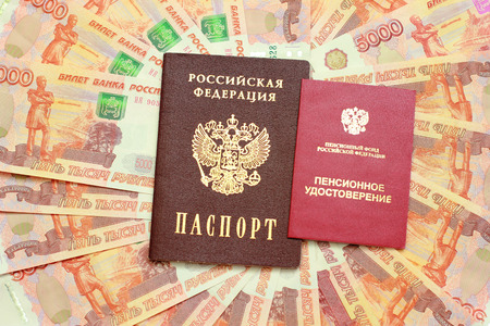 Russian passport and a pension certificate on the background of five thousandth money