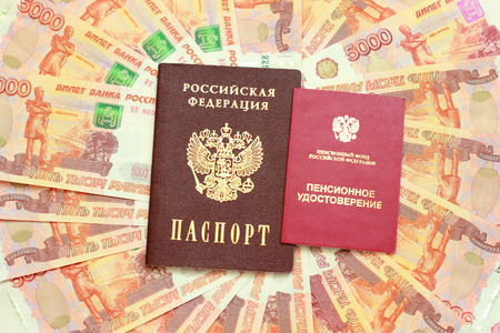 thousandth: Russian passport and a pension certificate on the background of five thousandth money
