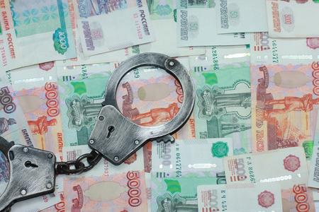 Handcuffs lie on Russian money