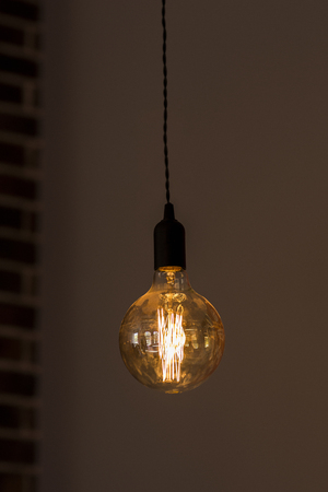 alone hanging bulb. the bulb burns. dark room. a lamp with a black socle.