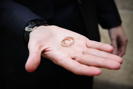 Wedding rings in the hand of the groom. Wedding gold rings on wedding day. 版權商用圖片