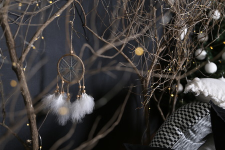 Dreamcatcher and branch trees against the background of a green fir-tree with white spheres and pieces of multi-colored pillows. Banque d'images