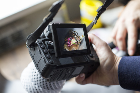 cake photo on the camera screen. the girl holds the camera in hand.