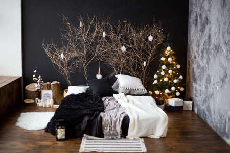 a bed with black and white linens against a dark wall with tree branches near the background and a garland. Christmas tree decorated with balloons near the bed.