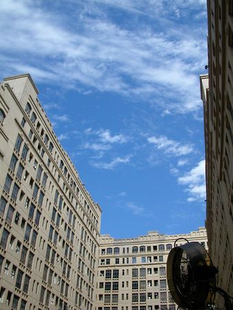 Three blocks of building framing a bluish sky