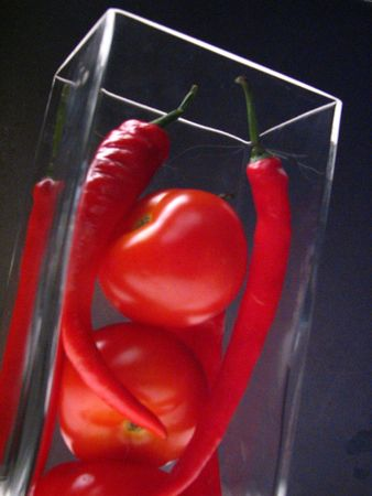 Chillies and tomatoes in a glass container on a black backdrop Stock Photo