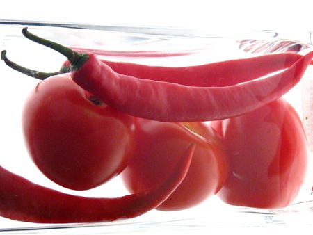 Chillies and tomatoes in a glass container on a white backdrop