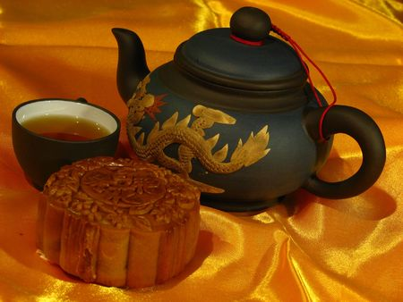 Profile of a Lotus-paste Mooncake, a Chinese teapot and a cup of tea on a golden wrinkly textile backdrop