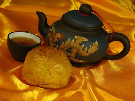Profile of a Shanghai Mooncake, a Chinese teapot and a cup of tea on a golden wrinkly textile backdrop