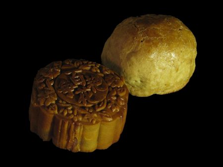 Profile of a Lotus-paste Mooncake and a Shanghai Mooncake on a dark backdrop