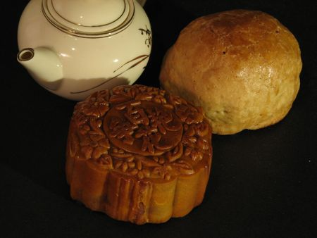 Profile of a Lotus-paste Mooncake, a Shanghai Mooncake and a Chinese teapot on a dark backdrop Stock Photo - 543689