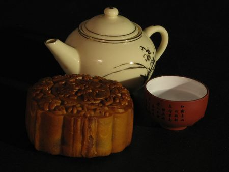 Profile of a Lotus-paste Mooncake, a Chinese teapot and a cup of tea on a dark backdrop