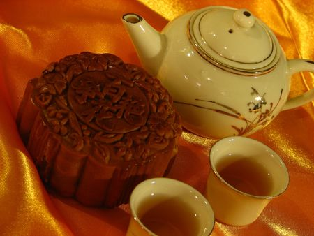 Profile of a Lotus-paste Mooncake, a Chinese teapot and two cups of chinese tea on a golden wrinkly textile backdrop