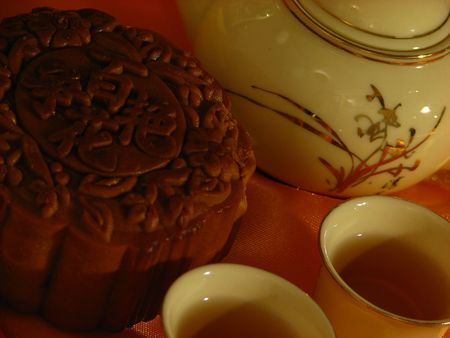 Close-up profile of a Lotus-paste Mooncake, a Chinese teapot and two cups of tea on a golden wrinkly textile backdrop
