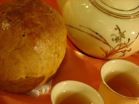 Close-up profile of a Shanghai Mooncake, a Chinese teapot and two cups of tea on a golden wrinkly textile backdrop