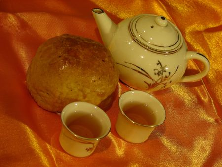 Profile of a Shanghai Mooncake, a Chinese teapot and two cups of tea on a golden wrinkly textile backdrop