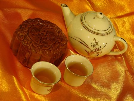 Profile of a Lotus-paste Mooncake, a Chinese teapot and two cups of tea on a golden wrinkly textile backdrop Stock Photo