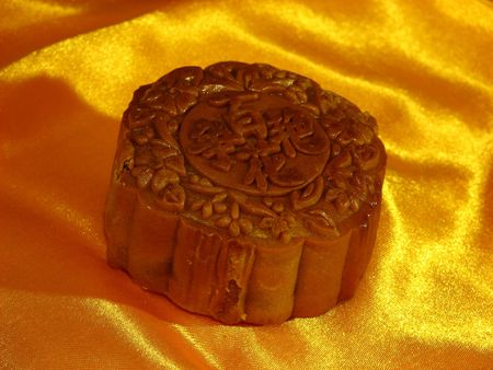 Profile of a Lotus-paste Mooncake on a golden wrinkly textile backdrop Stock Photo