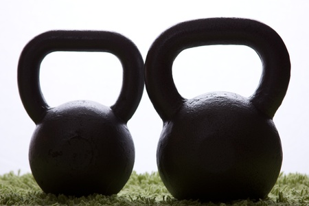 green carpet: Two kettlebell silhouette on a green carpet Stock Photo