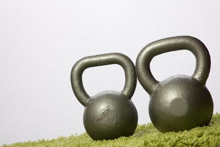 green carpet: Two kettlebells on a green carpet