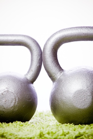 green carpet: Two kettlebells on green carpet cropped Stock Photo
