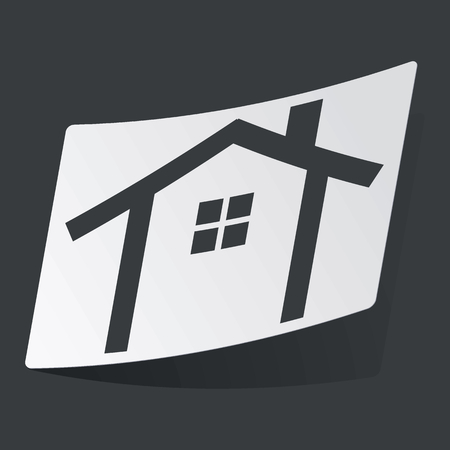 White sticker with black image of house contour, on black background