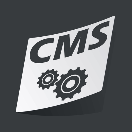 cms: White sticker with black text CMS and gears, on black background