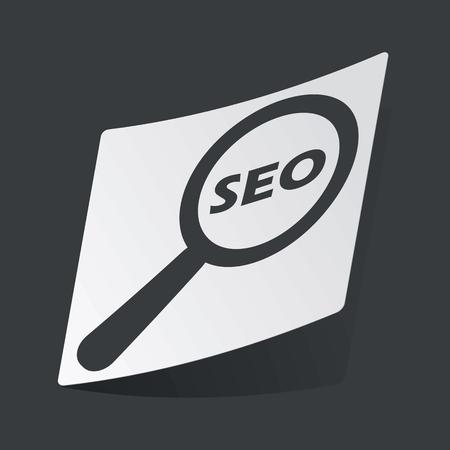 nuance: White sticker with black text SEO under loupe, on black background Illustration