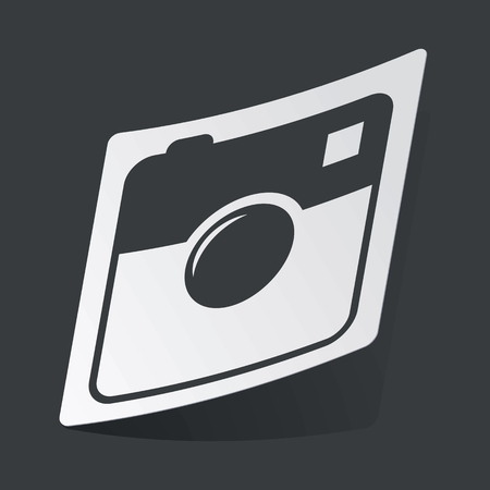 microblog: White sticker with black image of square camera, on black background