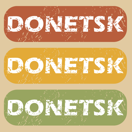 Set of rubber stamps with city name Donetsk on colored background