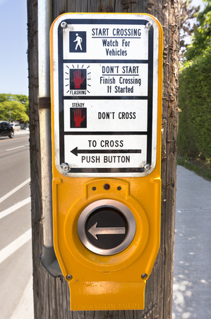 The closeup of the pedestrian crossing button or crosswalk signal button at a sidewalk in Toronto.