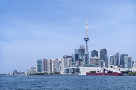 building cn tower: Toronto city skyline with CN tower and skyscrapers in front of Lake Ontario on a sunny day. Stock Photo