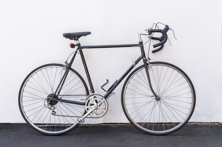 Ein Vintage Fahrrad Französisch Straße lehnte sich gegen die weiße Wand Hintergrund.