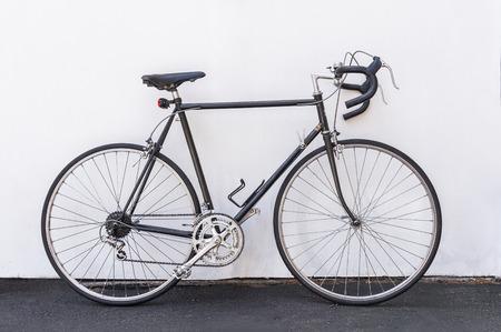Ein Vintage Fahrrad Französisch Straße lehnte sich gegen die weiße Wand Hintergrund. Standard-Bild
