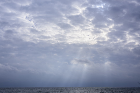 Glowing clouds in sky with rays of sunshine over Lake Ontario