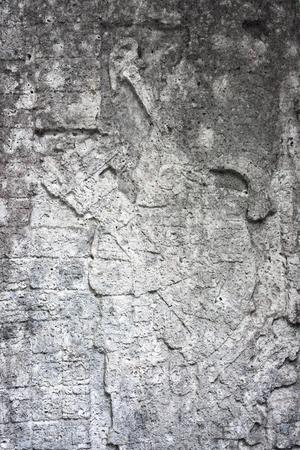 closeup detail of ancient weathered stone stele carving with fading image of a Maya king at Grupo Macanxoc Mayan Coba Ruins Yucatan Mexico Stock Photo