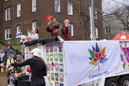 people on float promote Canada 150 at the Beaches Easter Parade 2017 on Queen Street East Toronto.