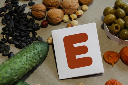 containing: Foods containing vitamin E : cucumber, olives, dried apricots, nuts, sunflower seeds and pumpkin seeds Stock Photo