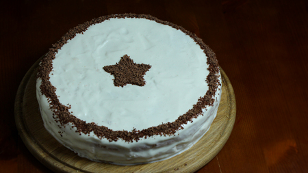 cram: Biscuit cake with sour cram and chocolade star on brown table Stock Photo